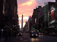 The sun paints the sky behind the obelisk on Av. Corrientes.